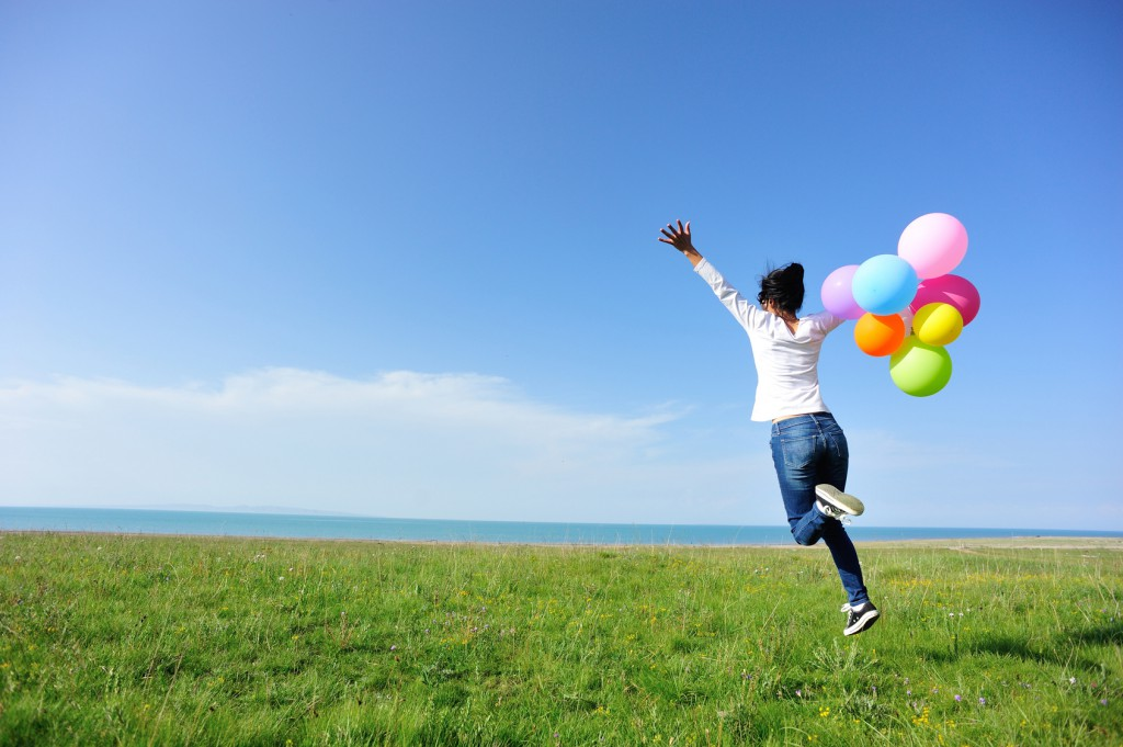 young asian woman on green grassland with colored balloons